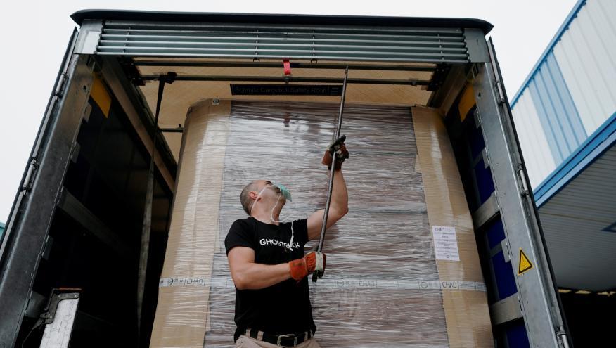 Un transportista de ataúdes cierra el espacio de carga de su camión en Valdemoro (Madrid)