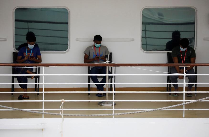 Tres personas con mascarillas en el crucero SuperStar Gemini en Singapur durante el coronavirus.