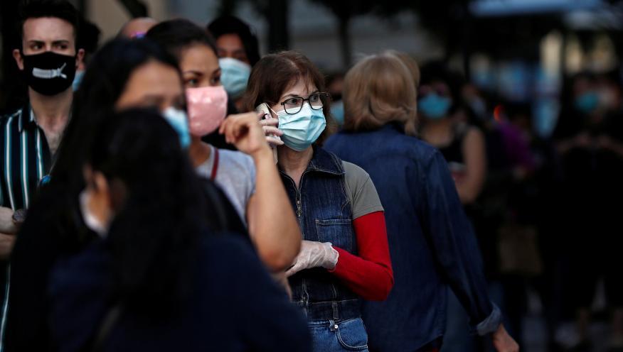 Varias personas con mascarilla hacen cola para entrar a una tienda Primark de Madrid