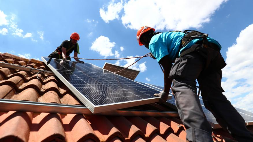 2 trabajadores instalan paneles solares en una vivienda en Colmenar Viejo (Madrid)