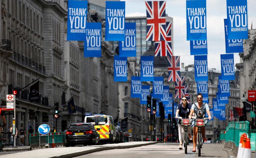 Ciclistas en Londres atraviesan una calle con carteles en agradecimiento por el comportamiento de la población durante la pandemia.
