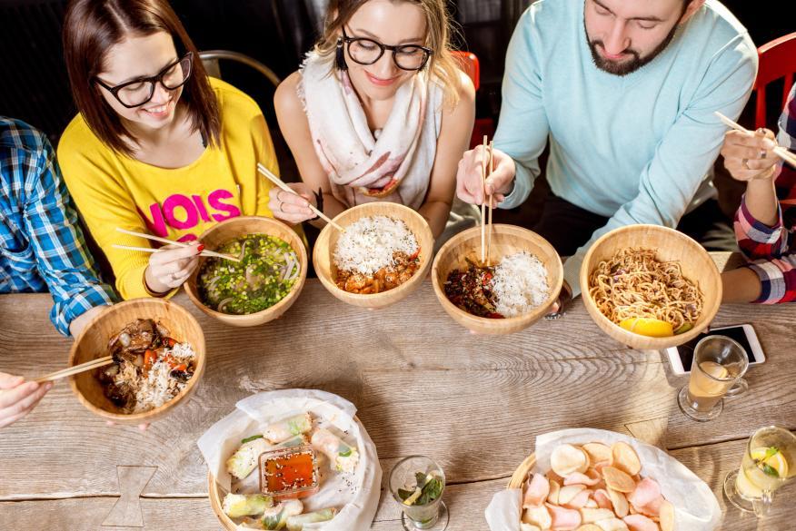 Grupo de jóvenes comiendo arroz.