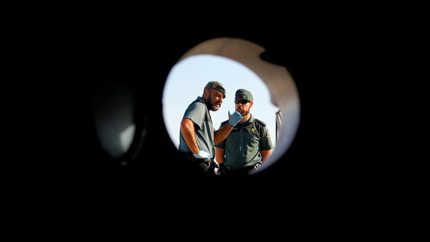Dos guardias civiles miran a través de una de las ventanas del barco de Proactiva Open Arms.
