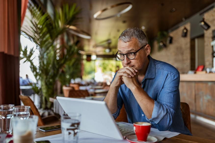Hombre sentado en una cafetería con su ordenador.