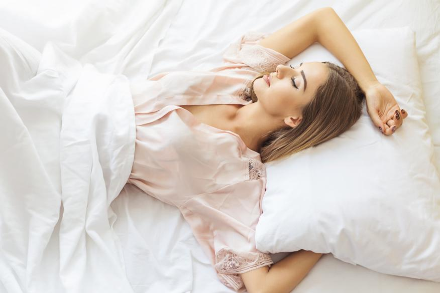 Una mujer duerme cómoda en sus sábanas.