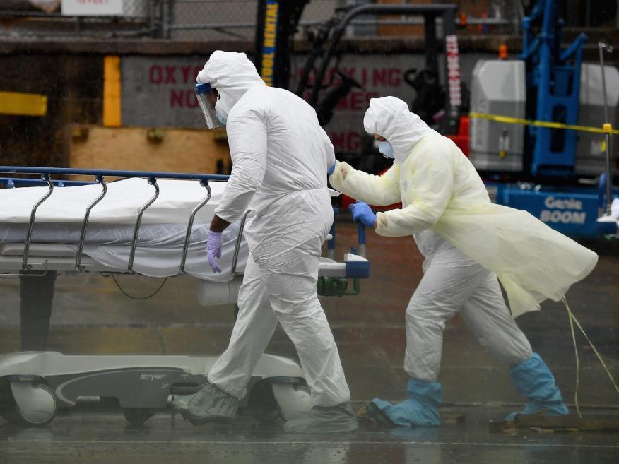 El personal médico traslada a un paciente fallecido a un camión refrigerado en el Brooklyn Hospital Center el 9 de abril en la ciudad de Nueva York, Estados Unidos.