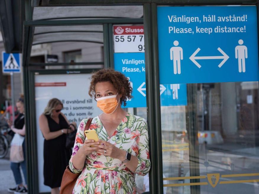 Una mujer lleva una mascarilla mientras espera en una parada de autobús el 26 de junio de 2020 en Estocolmo, Suecia.