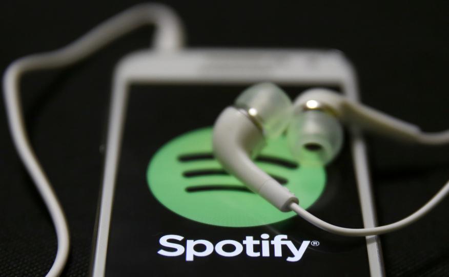 Unos auriculares sobre un móvil con el logo de Spotify