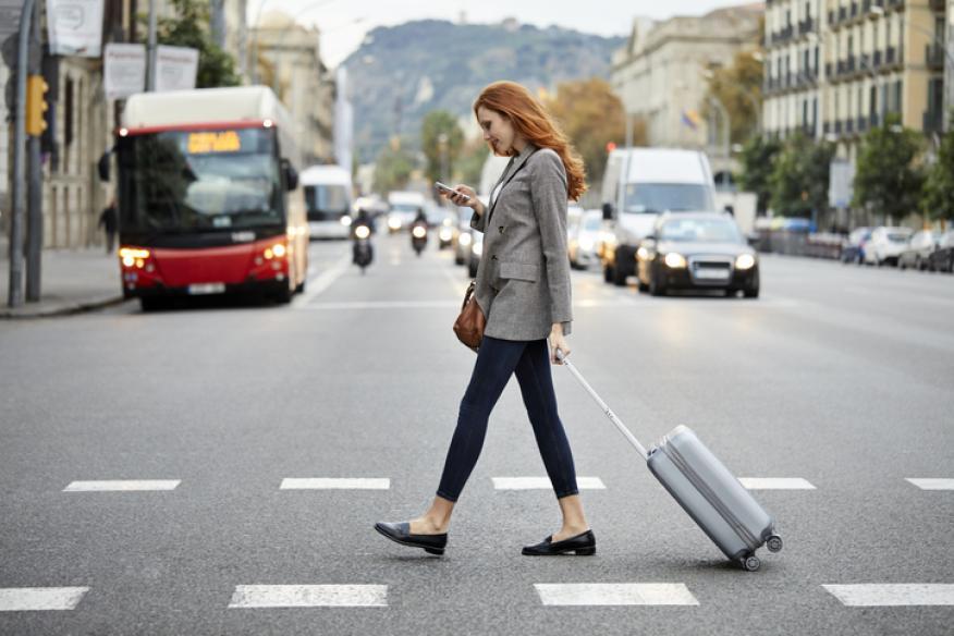 Mujer caminando mientras mira el móvil.