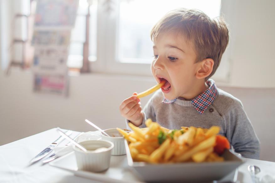 Niño comiendo patatas fritas