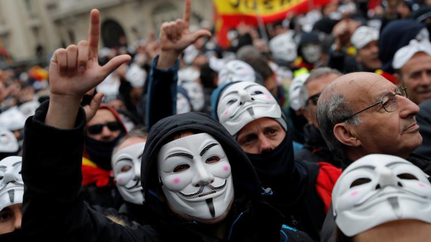 Manifestación de policías y guardias civiles por la equiparación salarial con una máscara de V de Vendetta, como el colectivo hacker Anonymous.