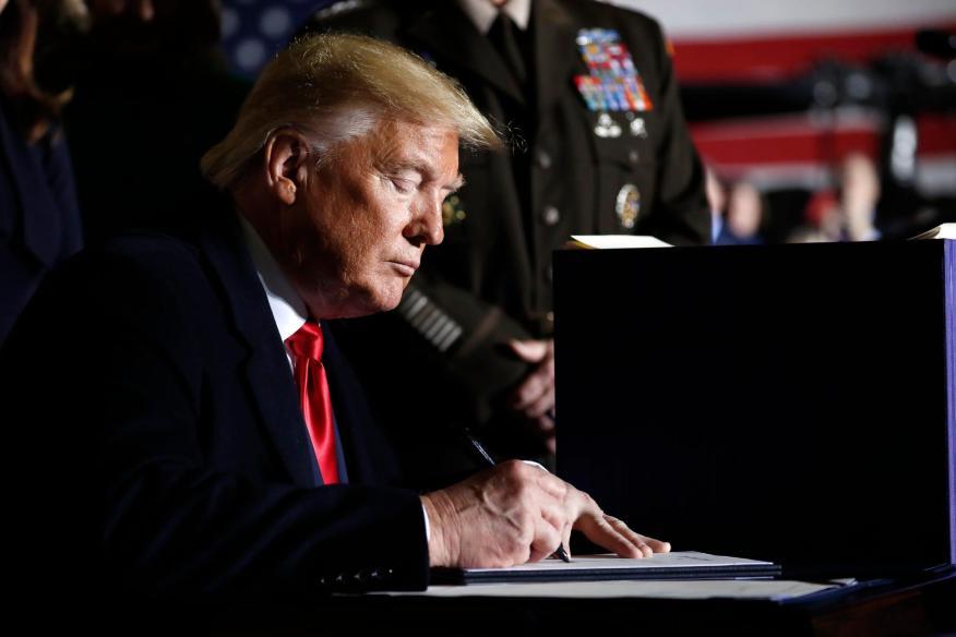 El presidente Donald Trump firma decretos en el Air Force One.