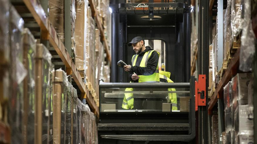 Un trabajador coloca paquetes con una carretilla montacargas en un almacén logístico