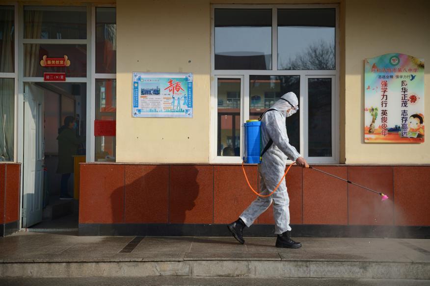 Un trabajador con traje protector rocía desinfectante en una escuela secundaria en Hohhot, China.
