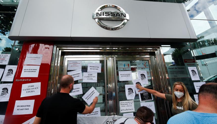 Trabajadores de Nissan pegan carteles contra el cierre de sus plantas en Barcelona en el escaparate de un concesionario de la marca nipona