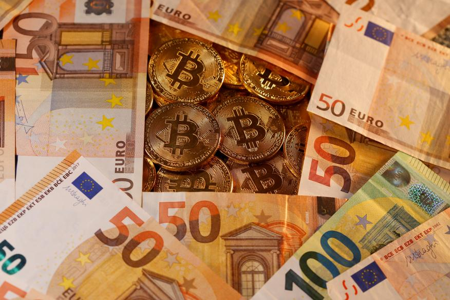 Billetes de euro junto a representaciones de bitcoins