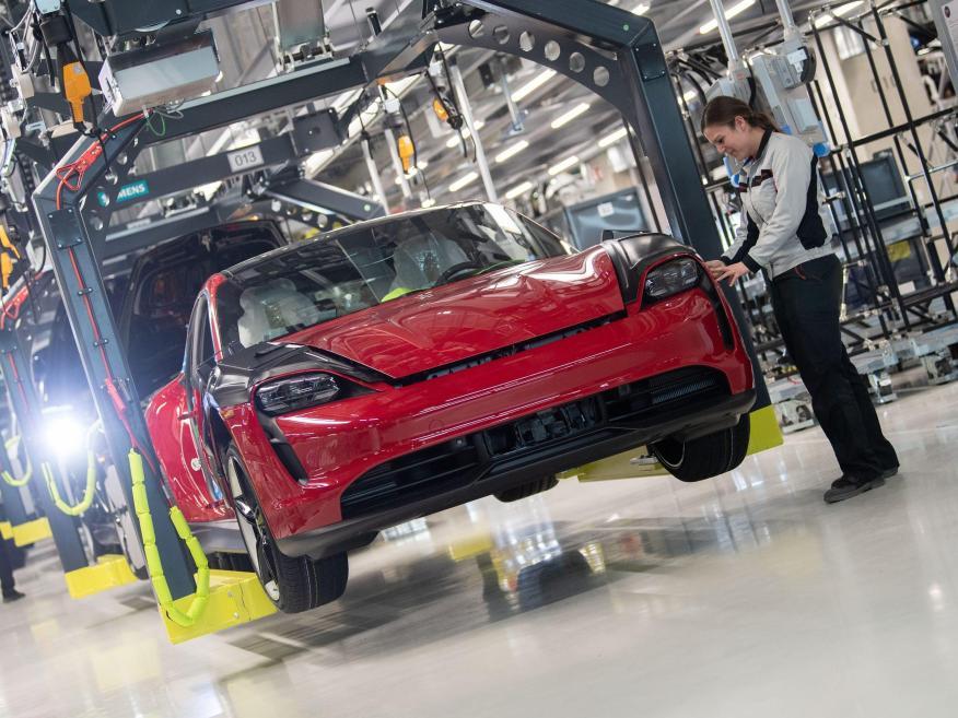An employee of Porsche AG checks a Porsche Taycan in production.
