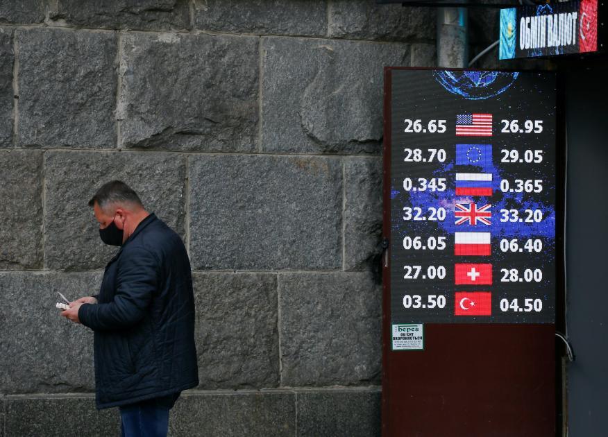 Un hombre frente a una sucursal de cambio de divisa.