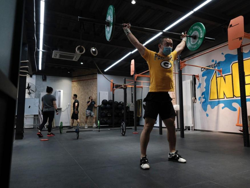 A man weight lifts in a mask at a reopened gym in Beijing. Fred Lee/Getty Images