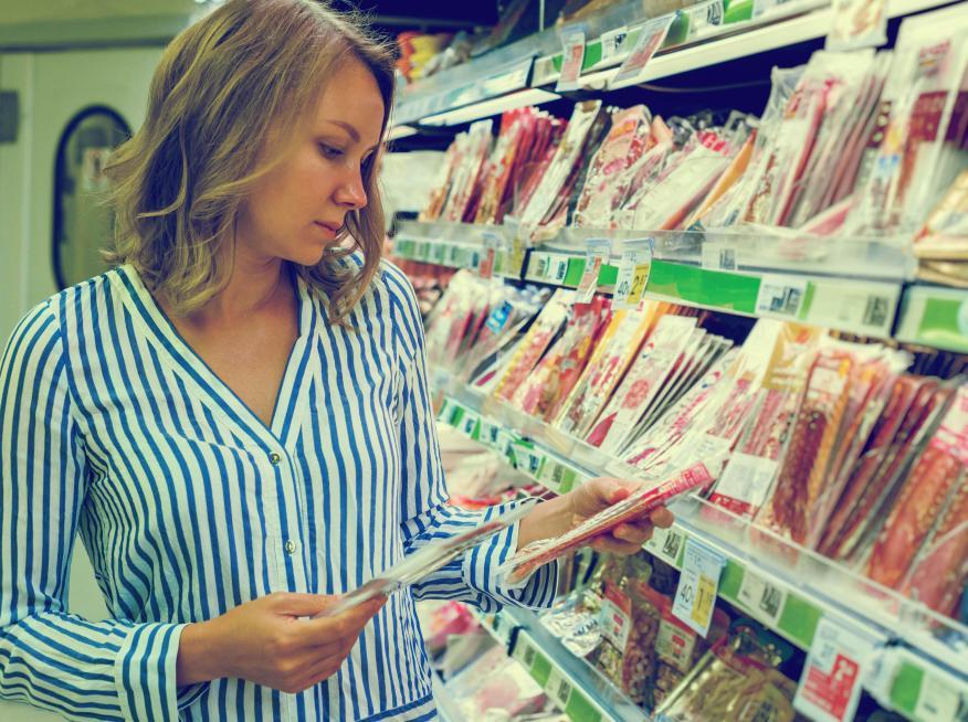 Mujer comparando productos en un supermercado