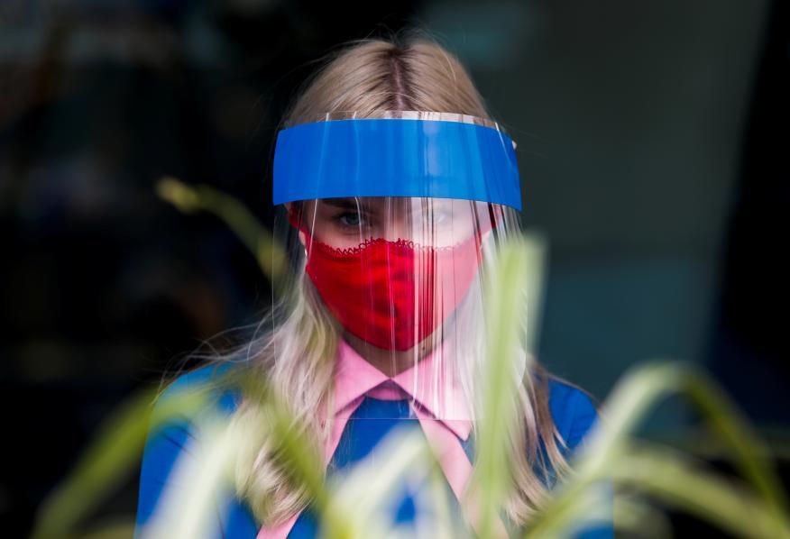 Una mujer utiliza una pantalla protectora facial para no contagiarse de COVID-19.