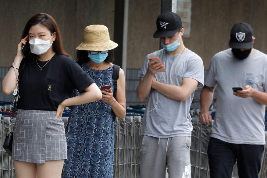 People wear protective face masks outside at a shopping plaza in Edgewater New Jersey, on July 8, 2020. Reuters