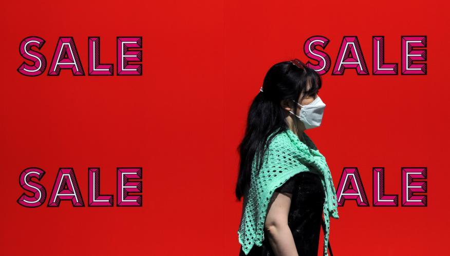 Una mujer pasa delante de un cartel de rebajas en Londres, Reino Unido, en plena pandemia del coronavirus.