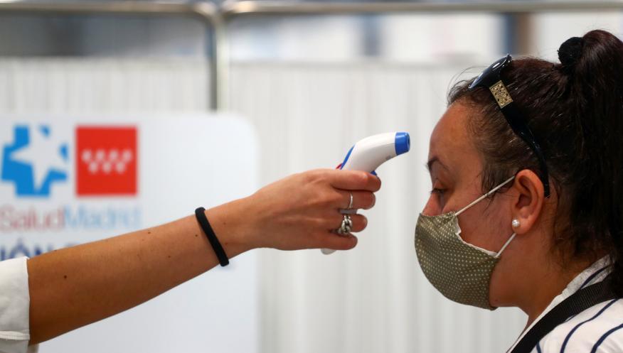 Una sanitaria toma la temperatura a una mujer a la entrada de un centro de atención primaria de Madrid