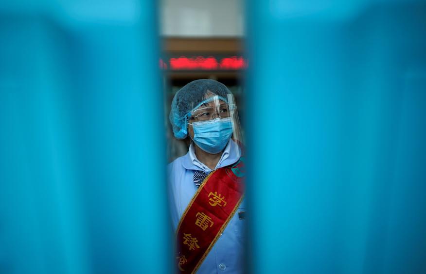 Un trabajador con mascarilla y protección facial en Wuhan durante la pandemia del coronavirus