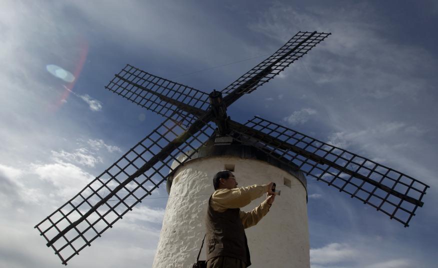 Un turista japonés se hace un selfie en un molino de viento en Consuegra (Toledo, Castilla-La Mancha)