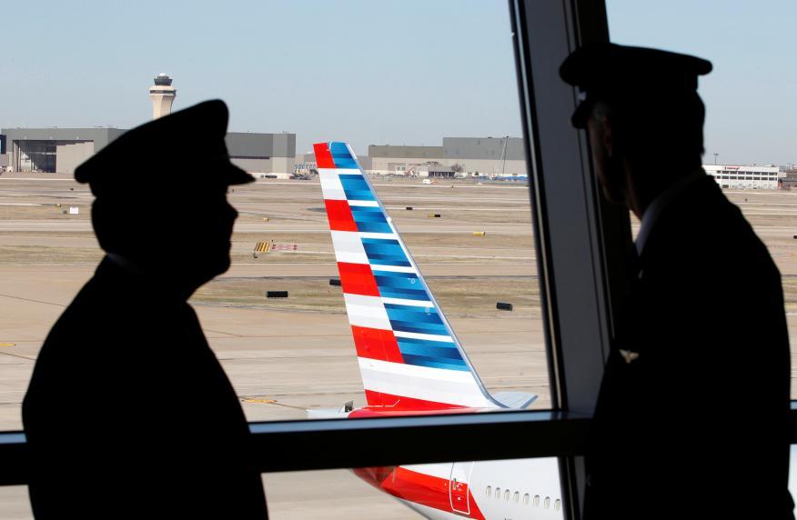 Pilotos hablan mientras observan un avión de American Airlines en el Aeropuerto Internacional de Dallas-Fort Worth, en Texas, EEUU.