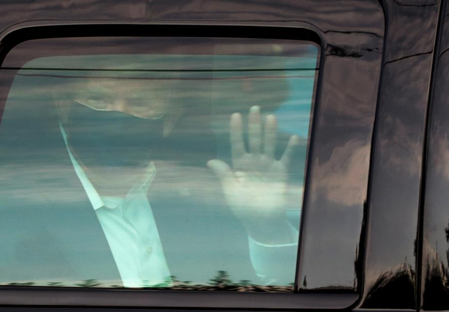 Donald Trump, presidente de Estados Unidos, saluda tras salir a dar un paseo dentro del coche en medio de su cuarentena por coronavirus.