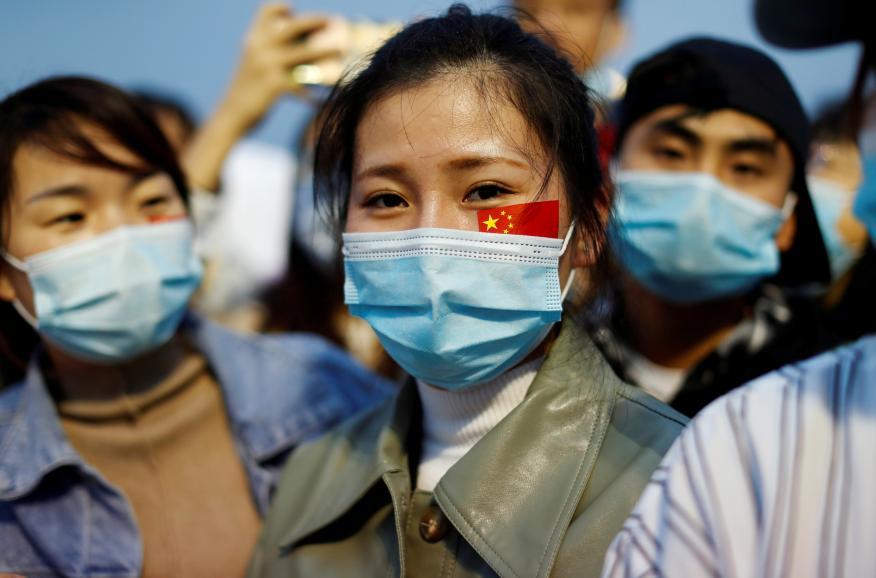 Mujer con mascarilla y la bandera de China