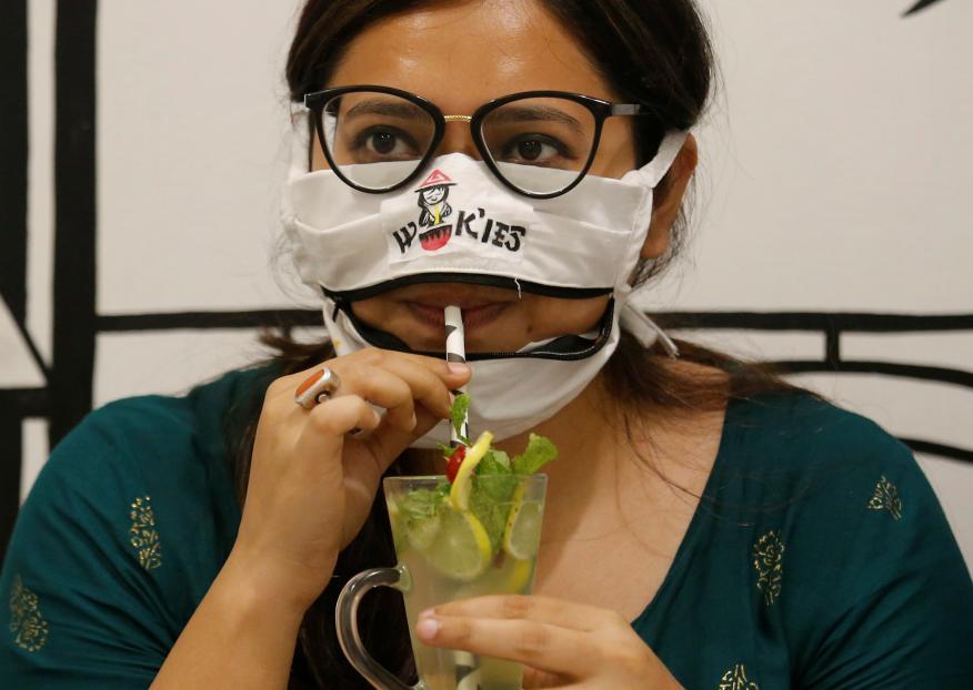 mujer con mascarilla bebiendo