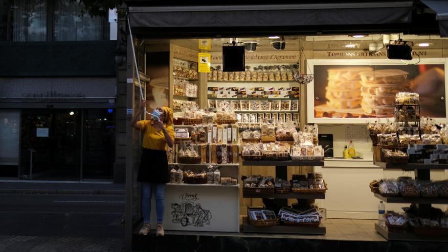 Una trabajadora levanta el toldo de su tienda en Barcelona