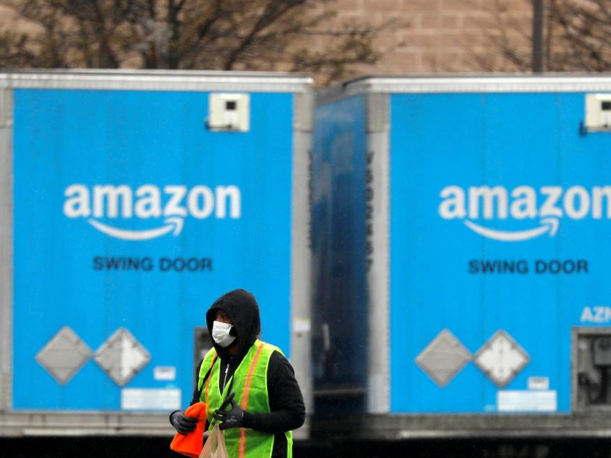 A worker in a face mask walks by trucks parked at an Amazon facility in Long Island, New York on March 17, 2020. REUTERS/Andrew Kelly/File Photo
