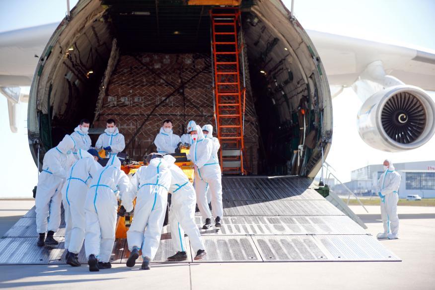 Un grupo de operarios trata de cargar suministros médicos en un avión durante la pandemia del coronavirus