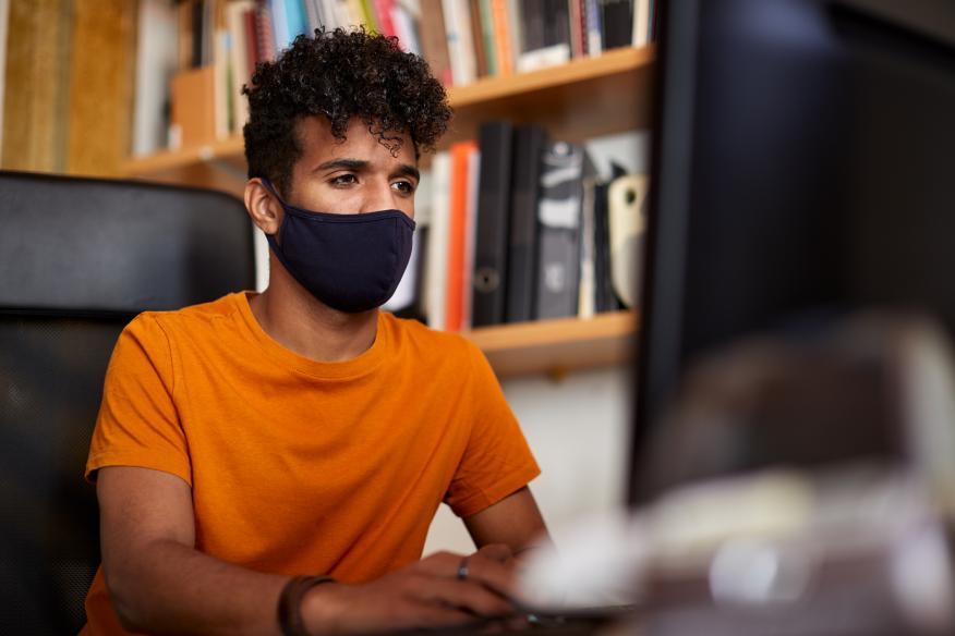 Un joven trabaja sentado frente a un ordenador con una mascarilla durante la pandemia del COVID-19