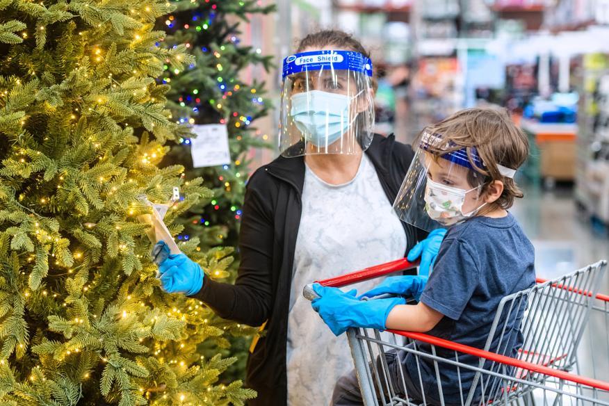 Madre e hijo con mascarillas comprando un árbol de Navidad.