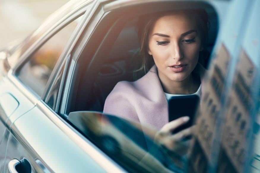 Mujer en el coche mirando el iPhone