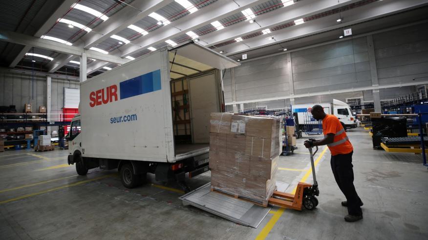 Un operario de Seur introduce un palé de paquetes en una furgoneta de reparto