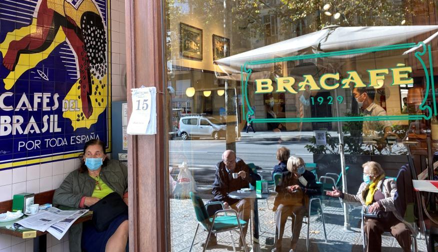 Varios clientes con mascarilla, en la terraza y el interior de un bar de Barcelona