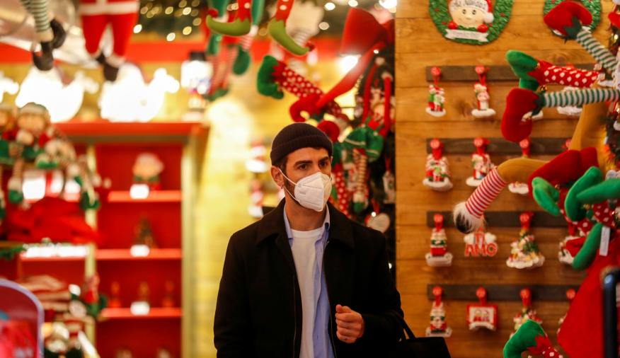 Un hombre con mascarilla de compras en un mercado navideño en Roma