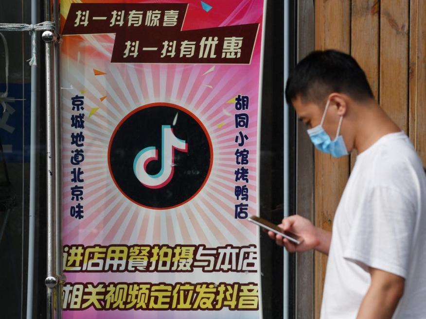Un hombre pasa junto a un restaurante con un logotipo de TikTok que se muestra en la ventana en Beijing el 14 de septiembre de 2020