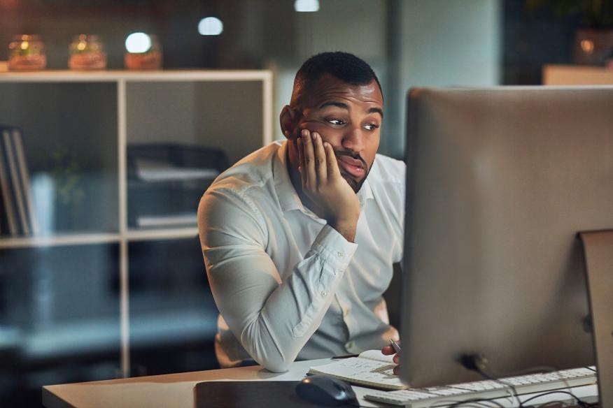 Un hombre triste mira su ordenador