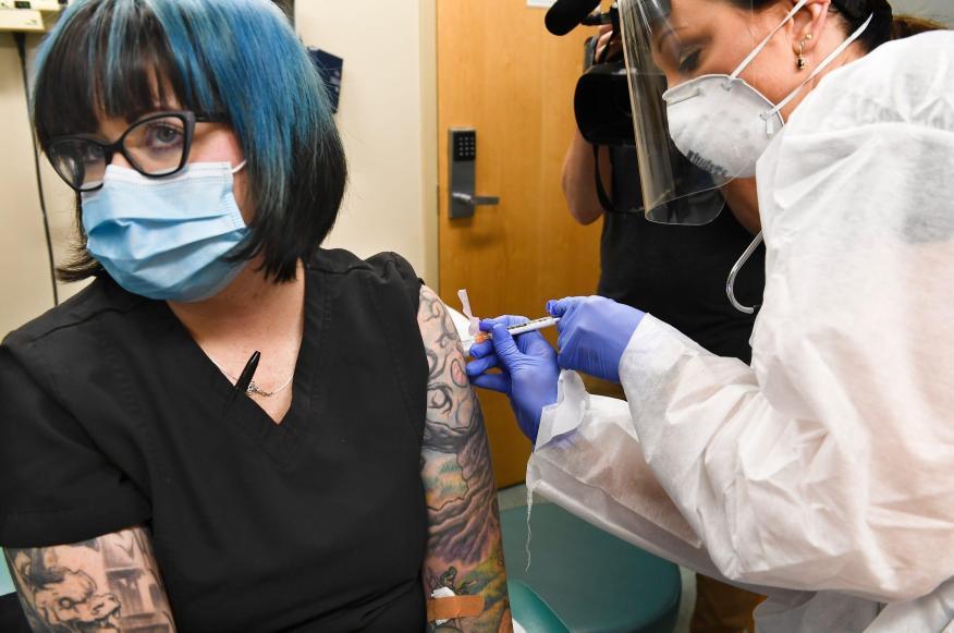 La enfermera Kath Olmstead, a la derecha, le da a la voluntaria Melissa Harting una de las inyecciones de los ensayos de la vacuna contra COVID-19, desarrollada por los Institutos Nacionales de Salud de EEUU y Moderna Inc., el 27 de julio de 2020.