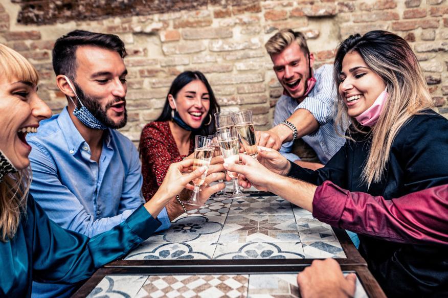 Varias personas brindan en un bar en época de coronavirus.