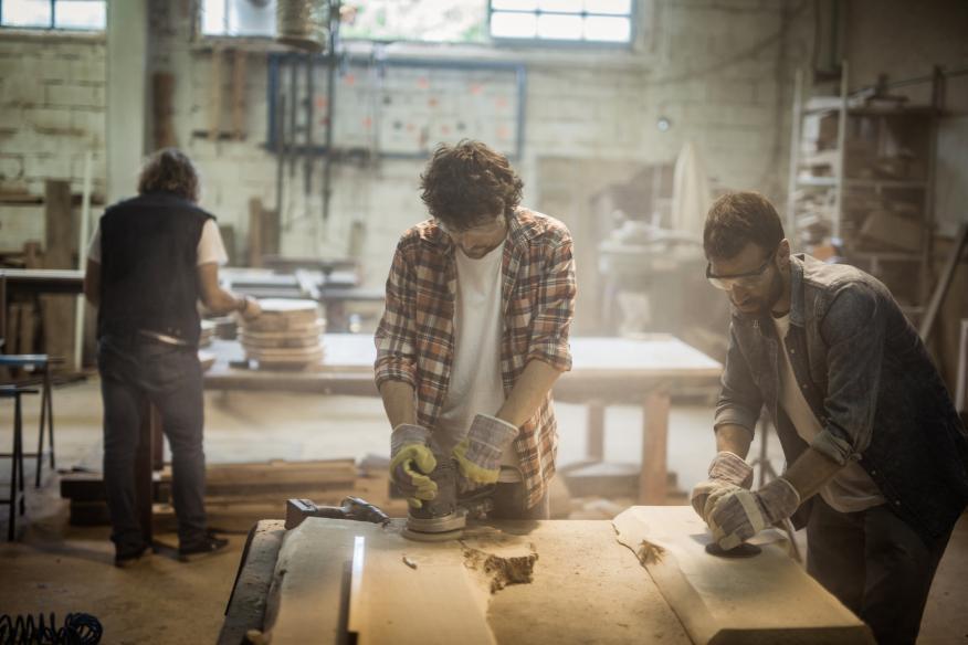 Varias personas trabajan en una carpintería.
