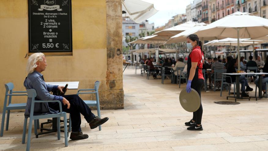 Una camarera joven atiende a un cliente jubilado en una terraza de Tarragona