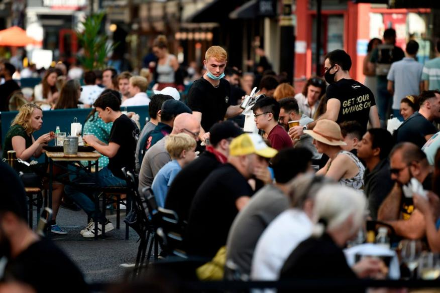 Customers eat lunch at tables outside restaurants in London, England, September 20, 2020.